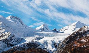 蓝天白云下的雪山山顶摄影图片