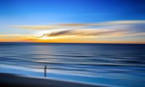 夕阳下在海边散步的男人摄影图片