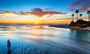 在海边沙滩上观看夕阳的情侣摄影图片