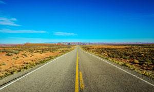 蓝天下通往远方的公路摄影图片