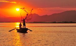 夕阳下的在湖泊上捕鱼的渔民摄影图片