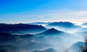蓝天下云雾缭绕的山峰摄影图片
