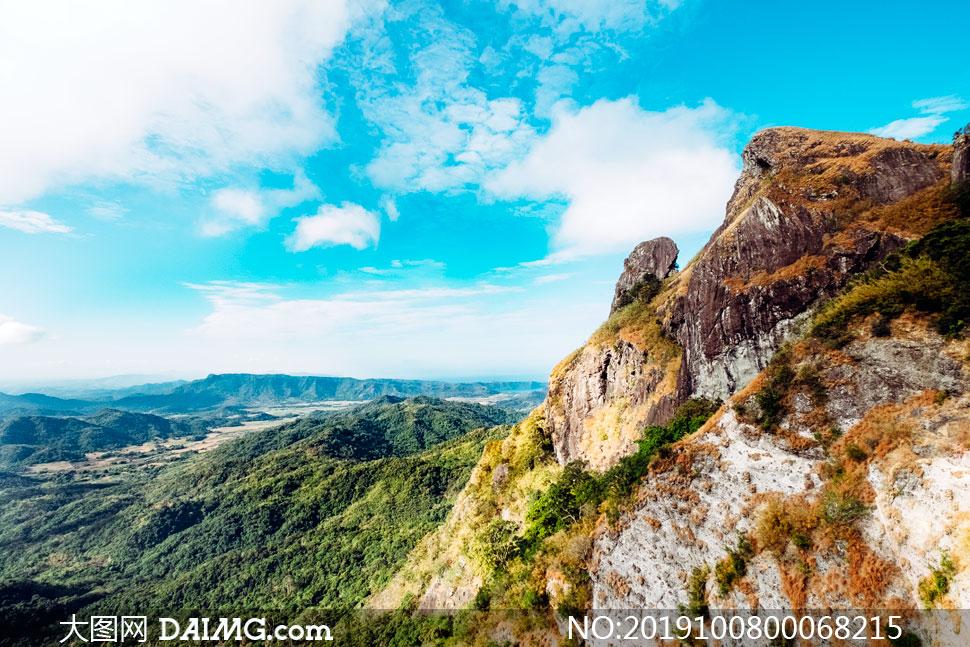 藍天下的山頂懸崖美景攝影圖片