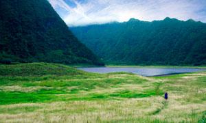 青山脚下的美丽湖泊和草地摄影图片