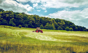 藍天白云下的農場拖拉機攝影圖片