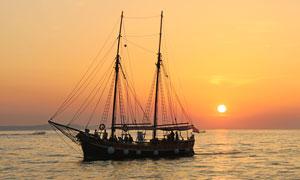 夕阳下在海边航行的帆船摄影图片