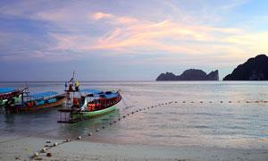 黄昏下在海边停泊的船只摄影图片