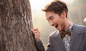 拿着粉笔在树上写字的男士原片素材