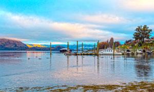 黄昏下湖边码头停靠的船只摄影图片