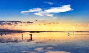 黄昏下在海边散步的游客摄影图片