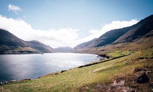 蓝天下山脚美丽的湖泊摄影图片