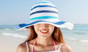 海边戴着帽子微笑的美女摄影图片