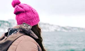 在海邊帶著紅色帽子的美女攝影圖片