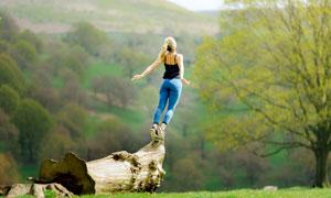在木桩上准备跳跃的美女摄影图片