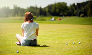 做在高爾夫球場上的美女攝影圖片
