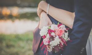 抱着新郎手拿花束的新娘摄影图片