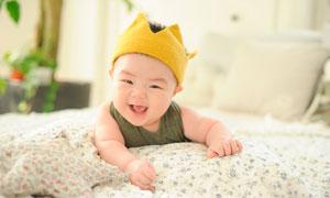 趴在床上微笑的可爱宝宝摄影图片