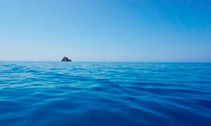 蓝天下海洋中的小岛摄影图片