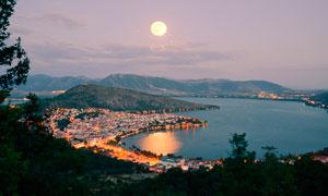 月光下的海边城市美景摄影图片