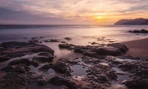 黄昏下的海边礁石美景摄影图片