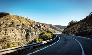 蓝天下山中弯曲的公路摄影图片