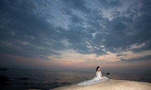 层层乌云礁石上的美女婚纱原片素材