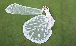 草地上仰望天空的美女婚纱摄影原片