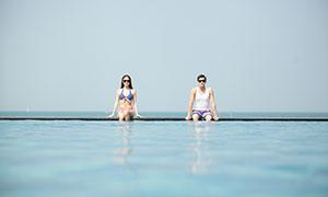 坐泳池边上的墨镜男女人物摄影原片
