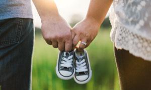 父母双手拿着童鞋高清摄影图片