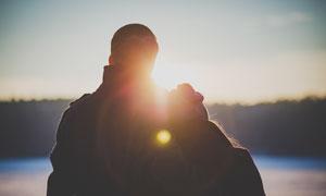 清晨相互依偎看日出的情侣摄影图片