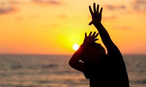 夕阳下海边儿童举手剪影摄影图片