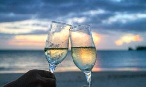 海边端着香槟酒举杯高清摄影图片