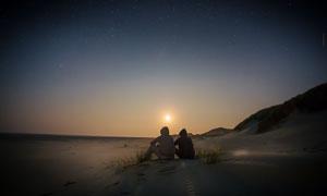做在海边沙滩上看日落的情侣摄影图片