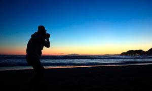 黄昏下在海边拍照的摄影师摄影图片