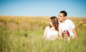做在草丛中的一家三口高清摄影图片