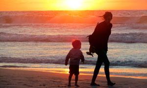 夕阳下在海边散步的母子剪影摄影图片