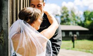 穿着婚纱搂着新郎的新娘摄影图片