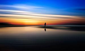 夕陽下的海邊站著的男子背影攝影圖片
