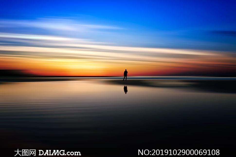 夕阳下的海边站着的男子背影摄影图片