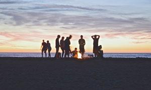 夕阳下在海边燃起篝火聚会的人摄影图