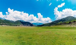 蓝天白云下的绿色草地高清摄影图片