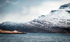 雪山下的湖泊和小屋攝影圖片