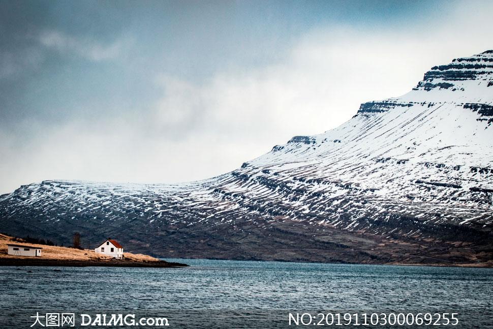雪山下的湖泊和小屋摄影图片
