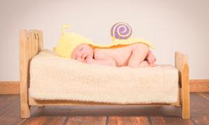 趴在床上睡覺的可愛寶寶攝影圖片