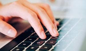 正在笔记本键盘上打字的人摄影图片