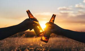 夕阳下举起酒瓶庆祝高清摄影图片