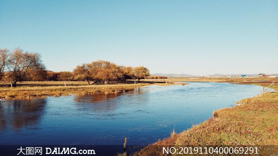秋季蓝天下的河流和树木摄影图片