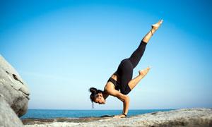 在海边做高难度瑜伽动作的女人摄影图片