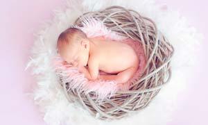 躺在籃子里熟睡的可愛寶寶攝影圖片