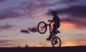 傍晚骑着自行车表演的小朋友摄影图片
